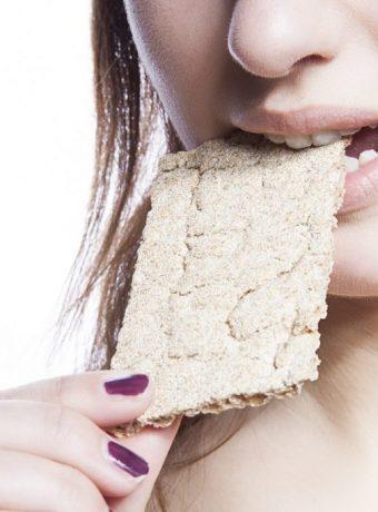 Detail shot of woman eating crispbread over white background